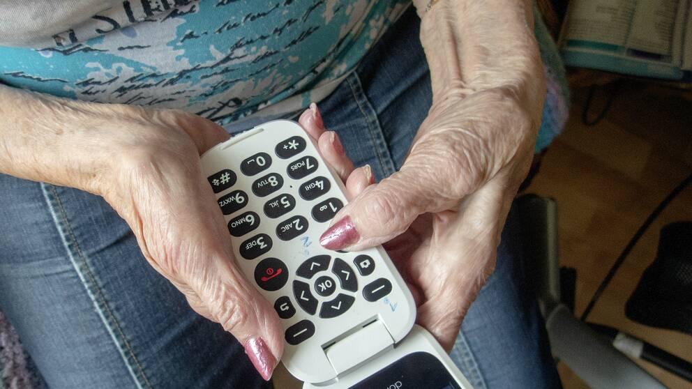 Kvinna håller i en knapptelefon.