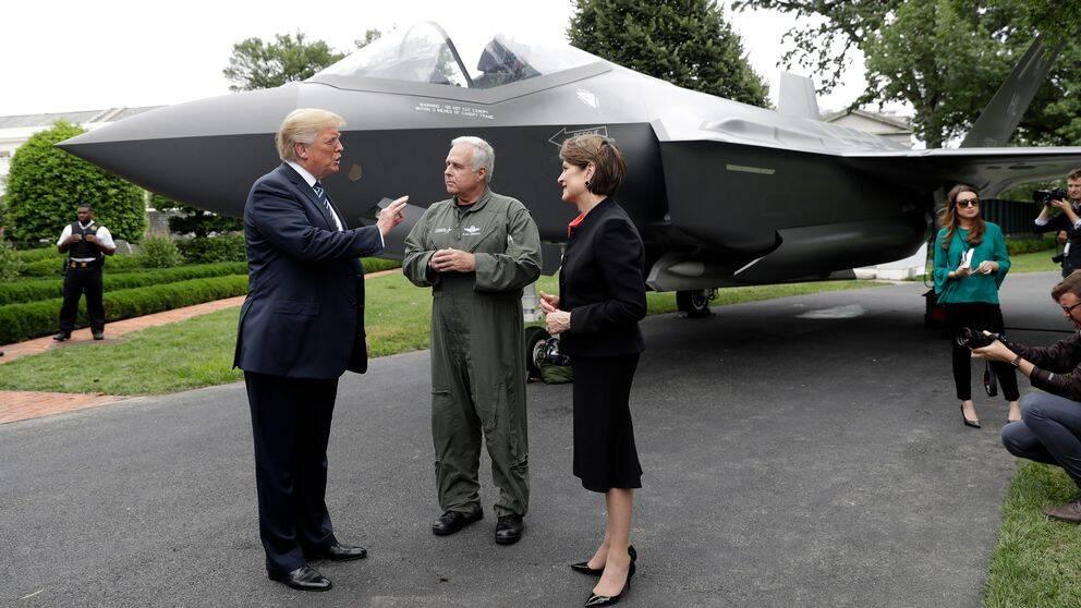 President Donald Trump tillsammans med Lockheed Martins styrelseordförande och vd Marillyn Hewson och en testpilot framför ett F-35 stridsflygplan i juli 2018.