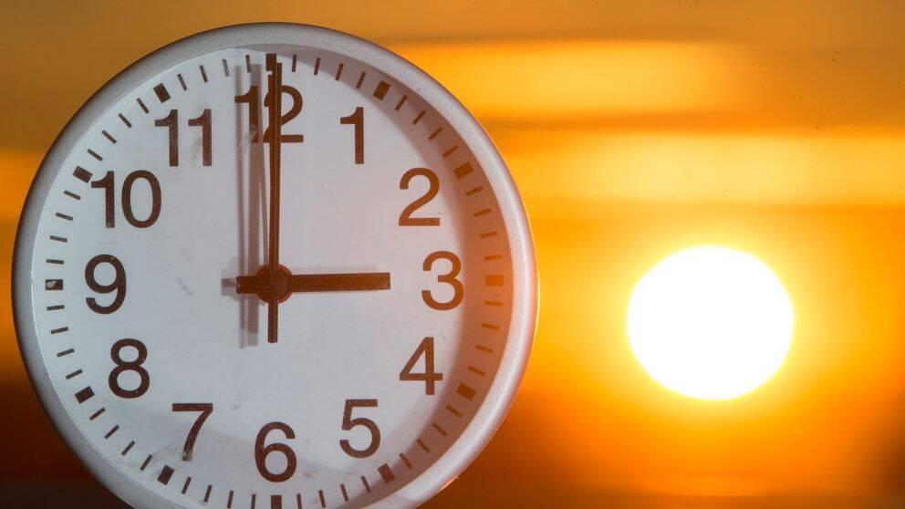 Bild på klocka med solen som går ner i bakgrunden. Nu är det dags att åter igen ställa om klockan efter årstiden. Men snart kan detta vara ett minne blott.