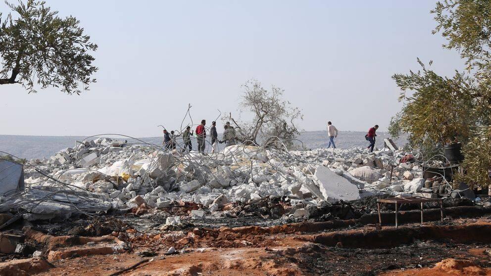 Människor undersöker platsen utanför byn Barisha som bombats sönder av helikoptrar.
