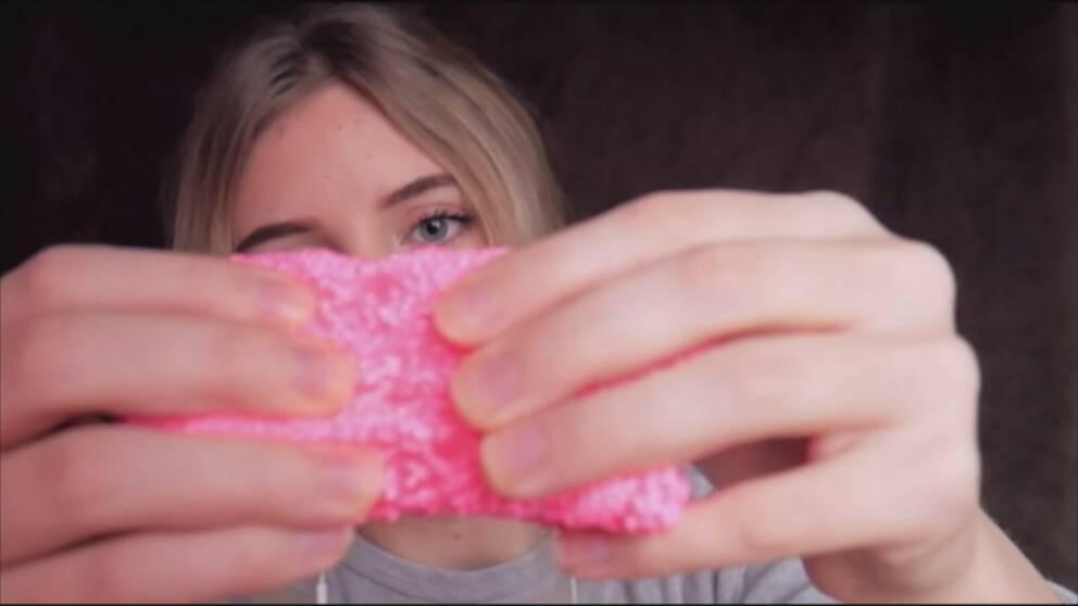 Kvinna håller rosa massa mellan händerna för att skapa ljud. ASMR
