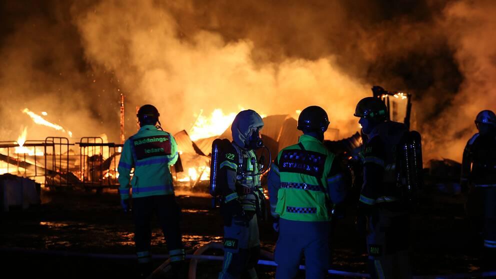 räddningspersonal framför resterna av en brinnande byggnad