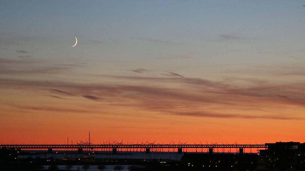 Lätta molnslöjor pyntar den röda kvällshimlen över Limhamn i Malmö, Skåne.