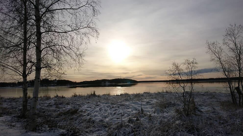 Solen skiner genom slöjmolnen. Ursviken i Västerbotten.
