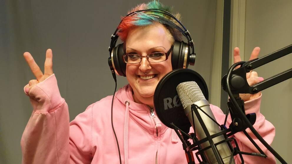 Marielle har hörlurar på sig och sitter i radiostudion framför en mick. Hon gör segertecken med fingrarna och ser glad ut.