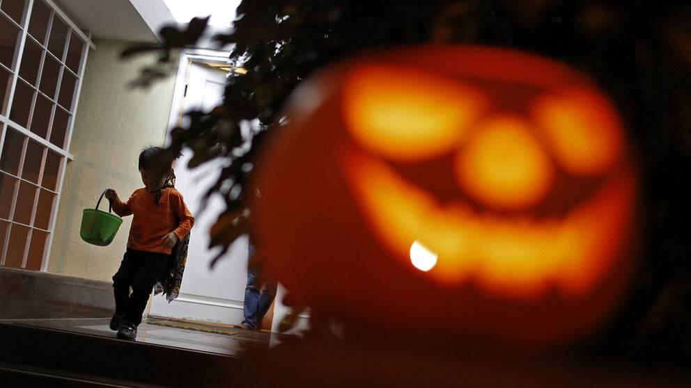 barn påväg från hus, med hink för godis, halloween-pumpa i förgrunden