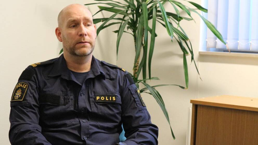 en polis sitter i ett rum