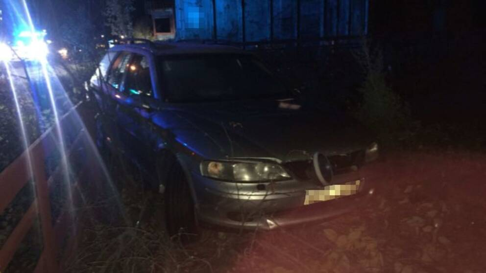 Bil med trasiga framljus som kört igenom ett staket