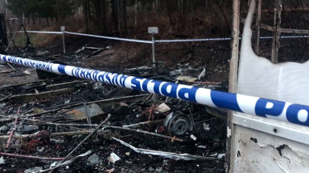 bränt skrot och polistejp på brandplatsen