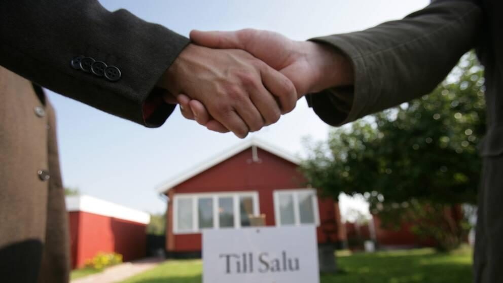 Två personer som skakar hand framför ett hus som sålts.