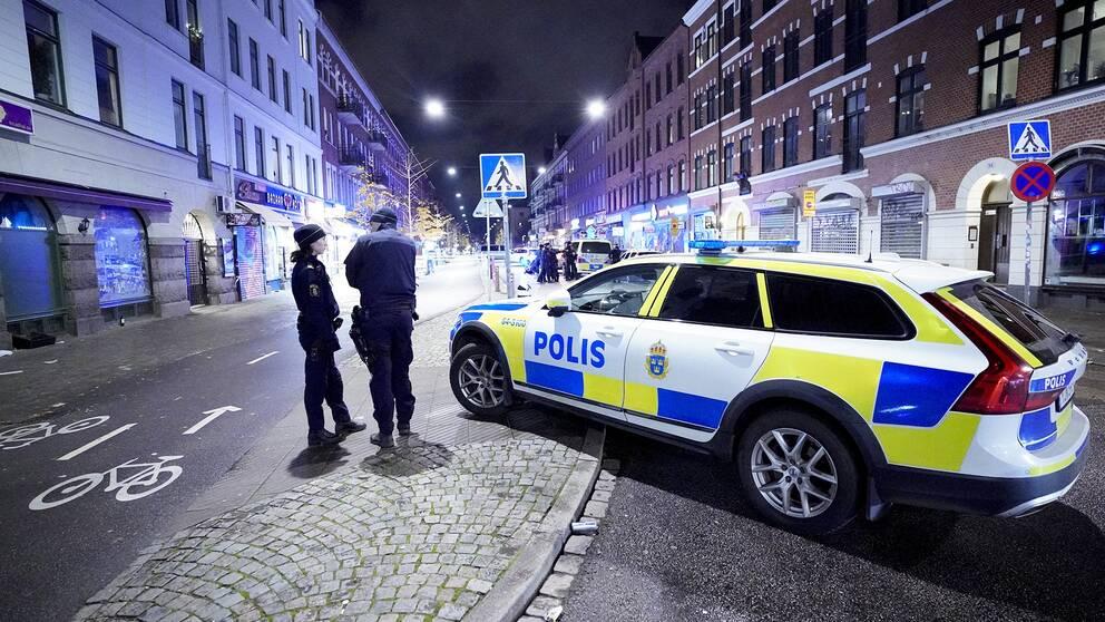 Poliser vid en polisbil.