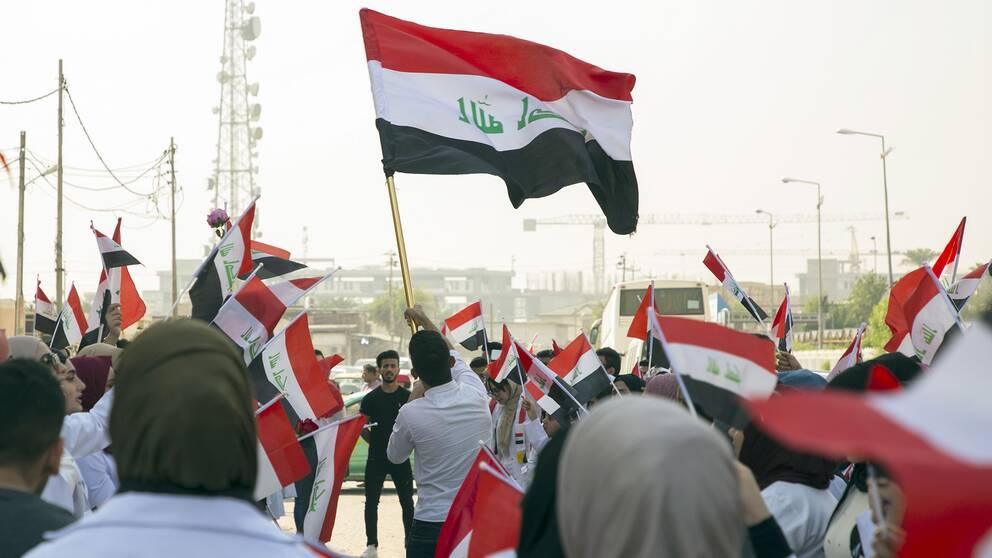 Demonstranter i Irak håller upp den irakiska flaggan.