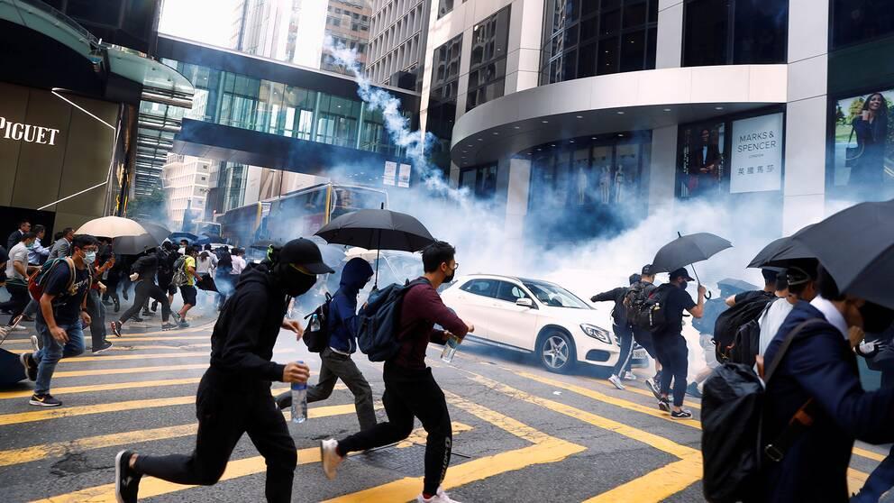 Människor springer för att skydda sig från tårgas under protester den 11 november i centrala Hongkong.