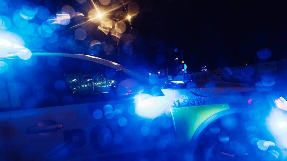 Polisbil med blåljus i mörker