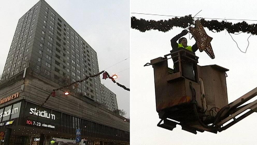 Bild på Krämar-höghuset med julpynt i förgrunden. Mannen står i skylift och hänger upp stor julstjärna.