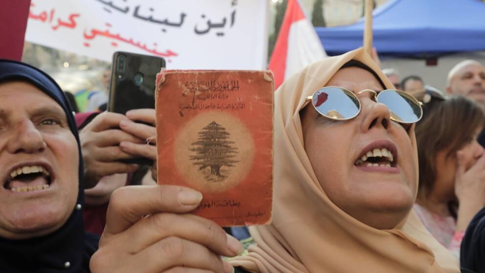 Kvinna håller upp en gammal libanesisk id-handling mitt under protesterna.
