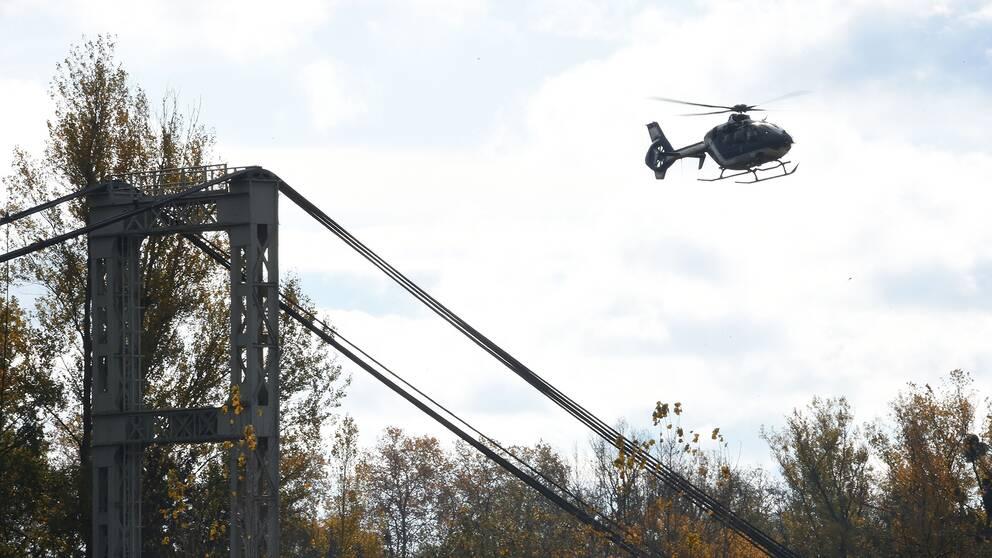 En helikopter flyger över en hängbro i en räddningsinsats.