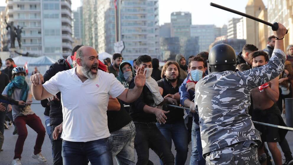 Polisen i Libanon tar till med batong när de försöker skingra den demonstrerande folkmassan.