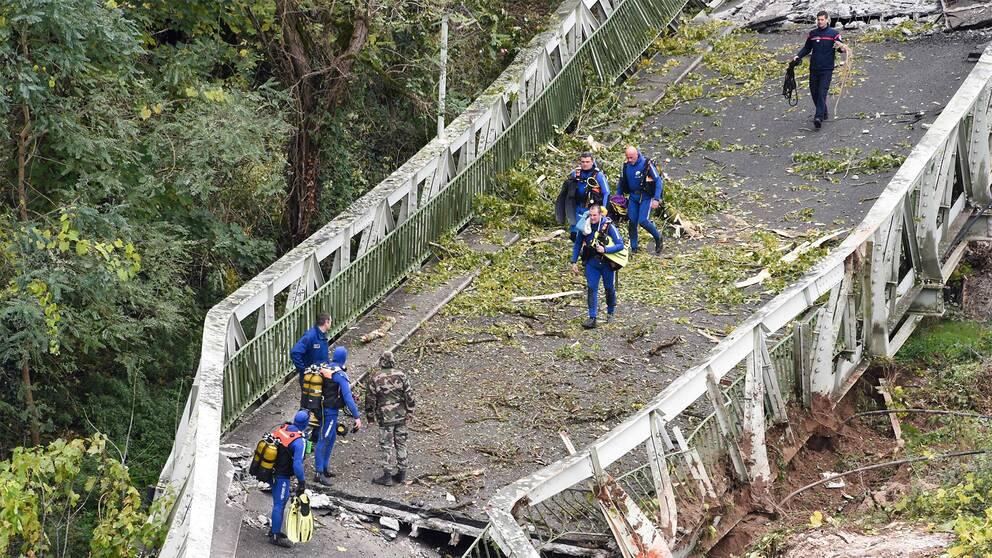 Räddningsarbetare går på en bro som har rasat.
