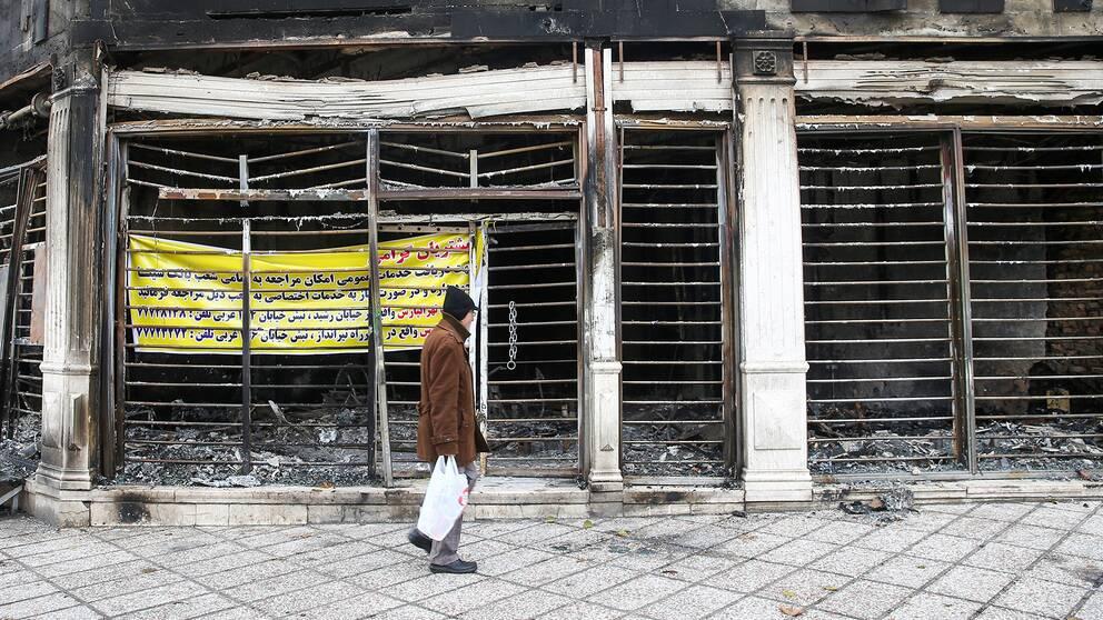 En man går framför en nedbränd bank i den iranska huvudstaden Teheran.