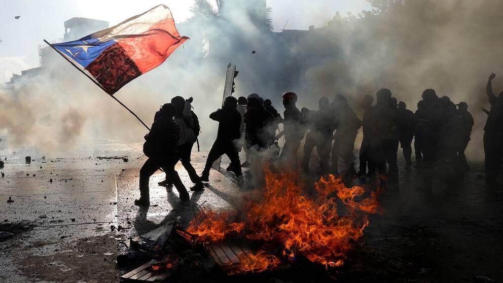 Demonstranter i Chile håller upp en chilensk flaga och står intill bråte som står i lågor.