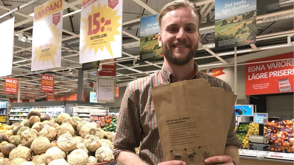 Joel Lundholm, avldeningschef över frukt och grönt i en Ica maxi-butik håller upp matavfallspåsar.