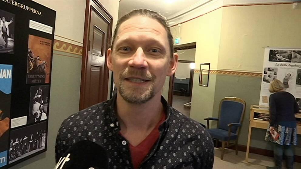 en leende man i en korridor i äldre lokal