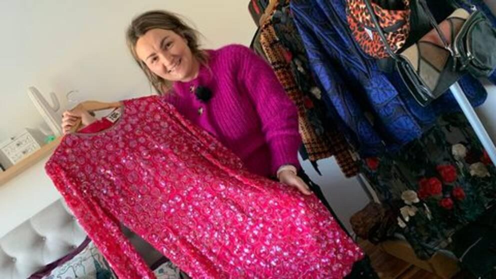 Kvinna håller fram en rosa paljettklänning