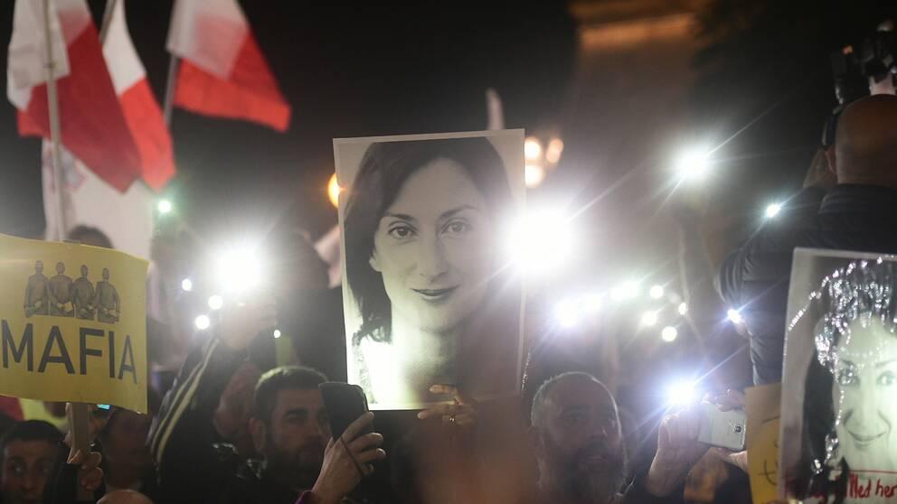 Demonstranter håller upp en bild på journalisten Daphne Caruana Galizia, under protester utanför kontoret till Maltas premiärminister, Joseph Muscat.