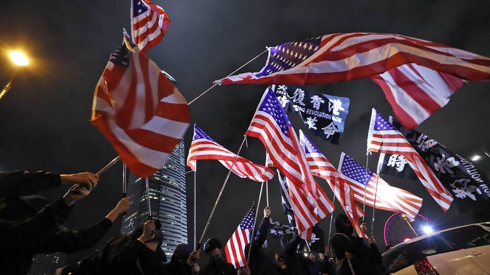 Demonstranter viftar med amerikanska flaggor under en demonstration i Hongkong.