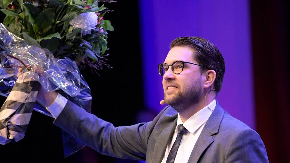 Jimmie Åkesson, Sverigedemokraternas partiledare håller i en blomma.