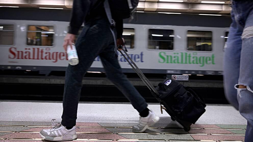 Person går med rullväska på perrong. I bakgrunden ett Snälltåg.