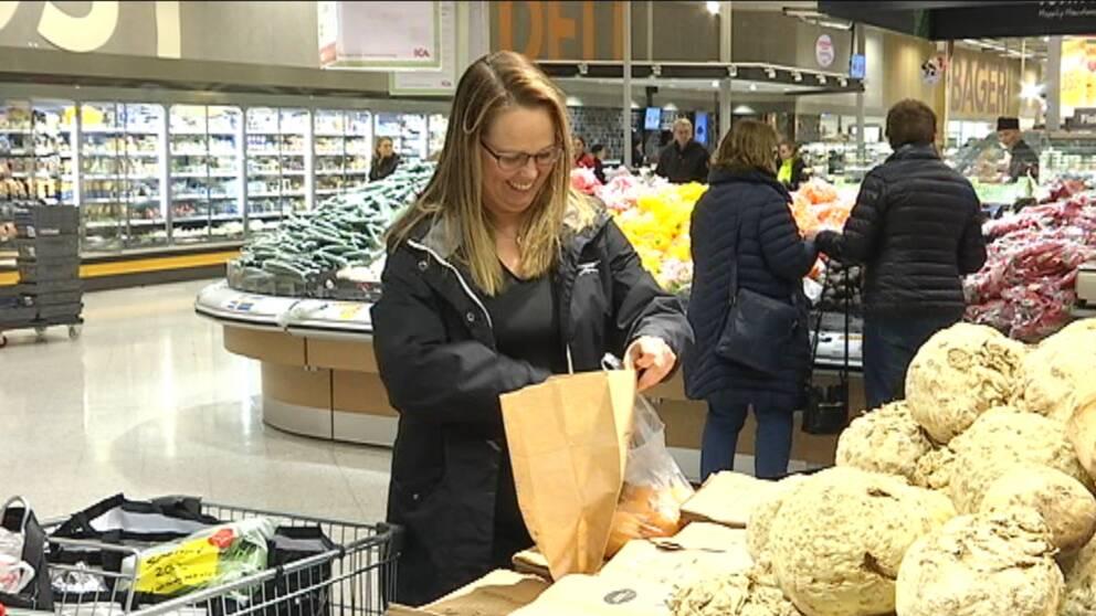 Camilla Gartz står i en butik och plockar i frukt i en matavfallspåse