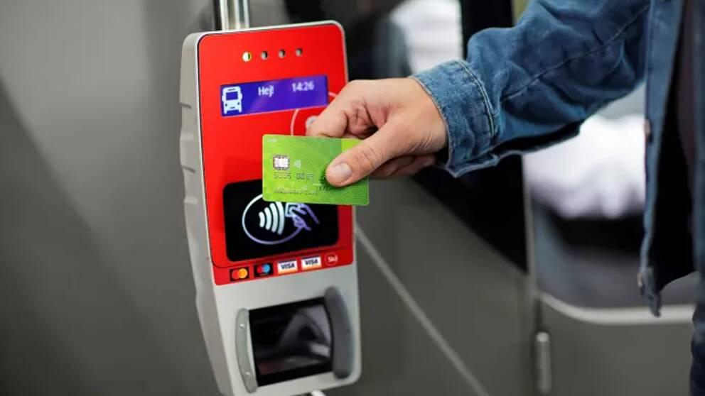 Person håller upp betalkort mot kortläsare ombord på en buss.