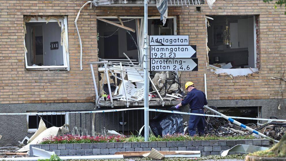 Husfasad med trasiga balkonger och fönster. En polis med gul hjälm undersöker bråte på en balkong.
