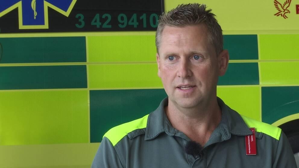 Daniel sitter sjukvårdsklädd framför en ambulans