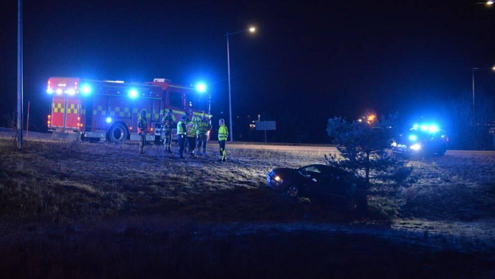 En brandbil står på vägen och i diket nedanför vägen står en bil med lysen på.