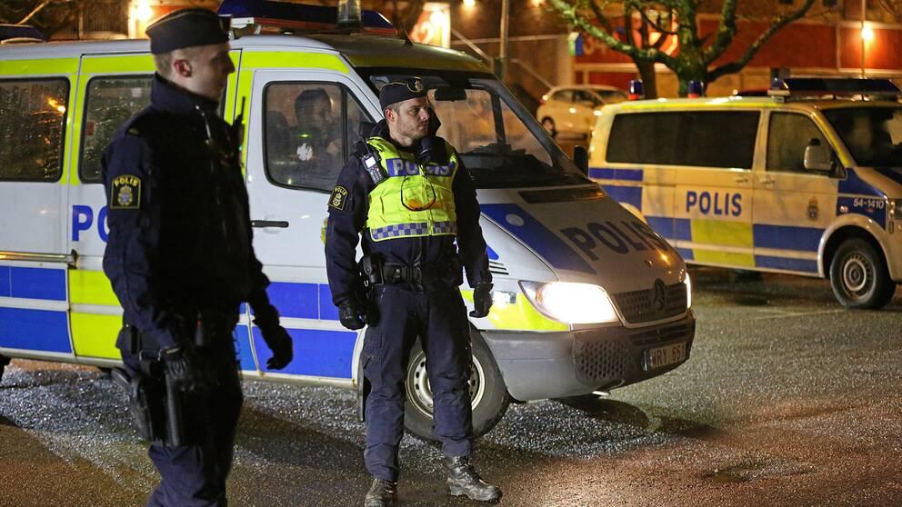 Poliser framför två polisbilar i Trollhättan
