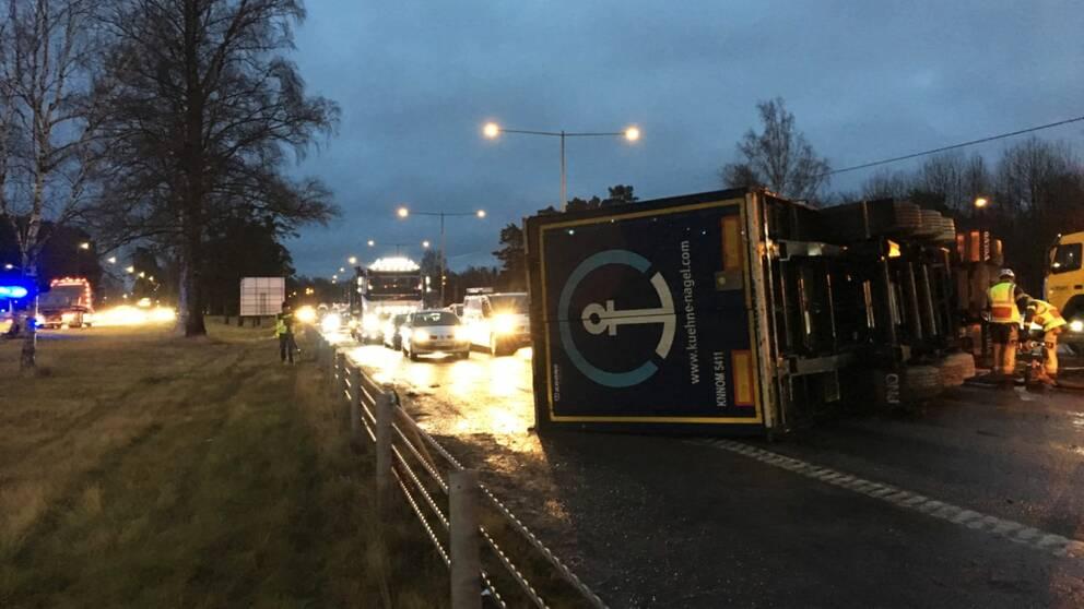 Lastbil ligger vält på sidan över en motorväg. Blåljuspersonal jobbar.