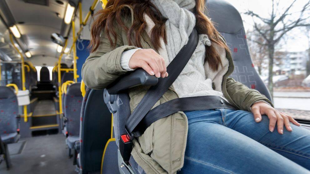 Kvinna på buss som har på sig bilbälte