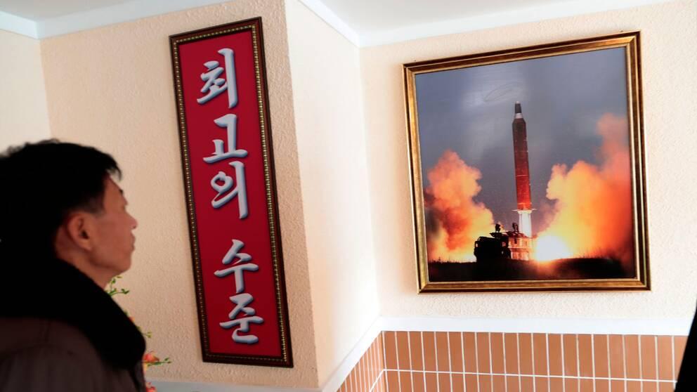 En arbetare i Pyongyang tittar på ett fotografi av ett robottest som hängts upp i fabrikslokalen.