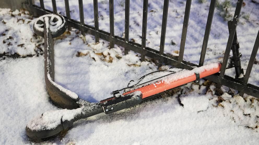 Elsparkcykel på gatan i snön