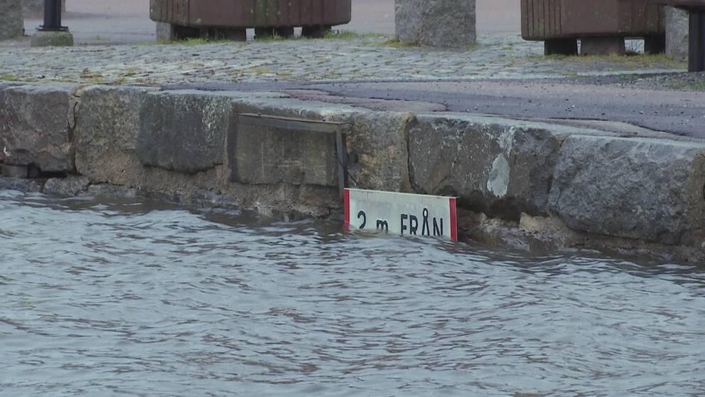 Skylt på kajkanten som knappt syns eftersom vattnet går så högt.