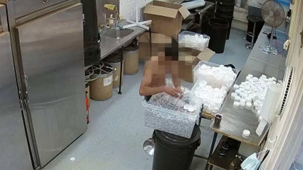 """Foton från polisens utredning visar hur svartarbetarna, som i de flesta fall fått 50 kronor i timmen i lön, packar snusdosorna i bar överkropp och utan handskar. """"Det här handlar även om konsumentens hälsa"""", säger åklagare Daniel Larson."""