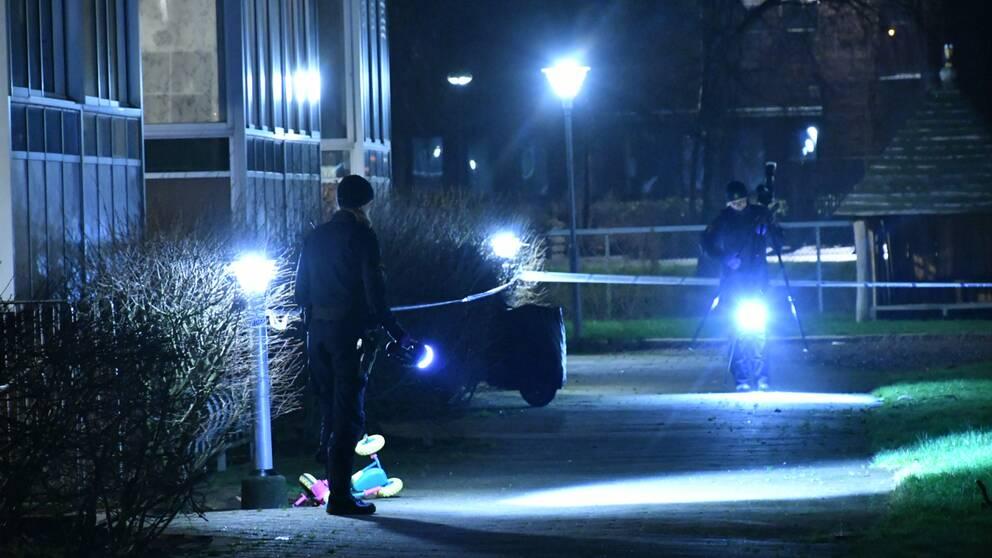 Poliser lyser med lampor för att kunna leta spår efter en skjutning som ägt rum under morgonen.