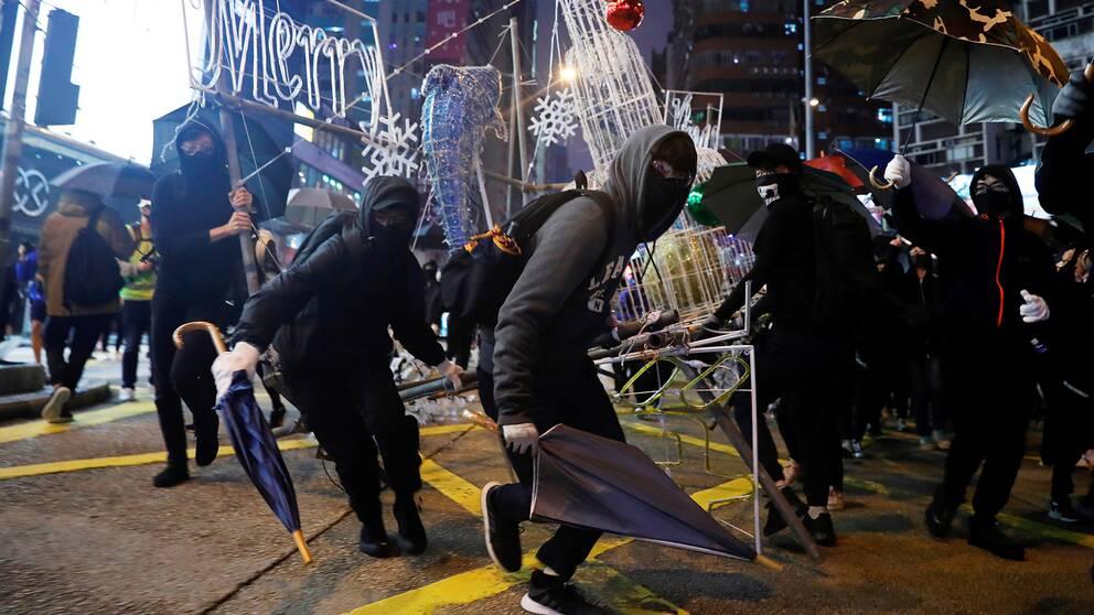 Demonstranter i Hongkong river ned jul- och nyårsdekorationer under en demonstration på nyårsafton.