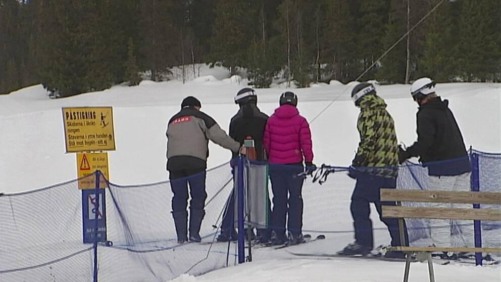 en liftgubbe hjälper skidåkare ta ankarlift