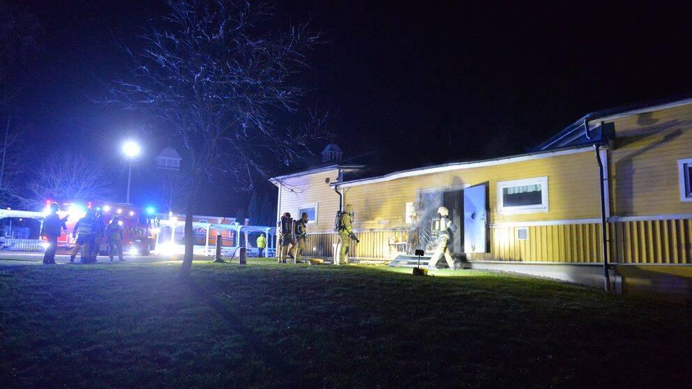 Brandbilar och brandmän står utanför samlingslokal, en gul träbyggnad. Det ryker från dörren.