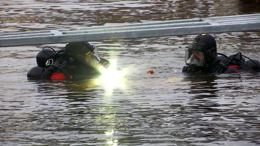 Två män i vattnet i dykutrustning men ficklampa som lyser in i kameran