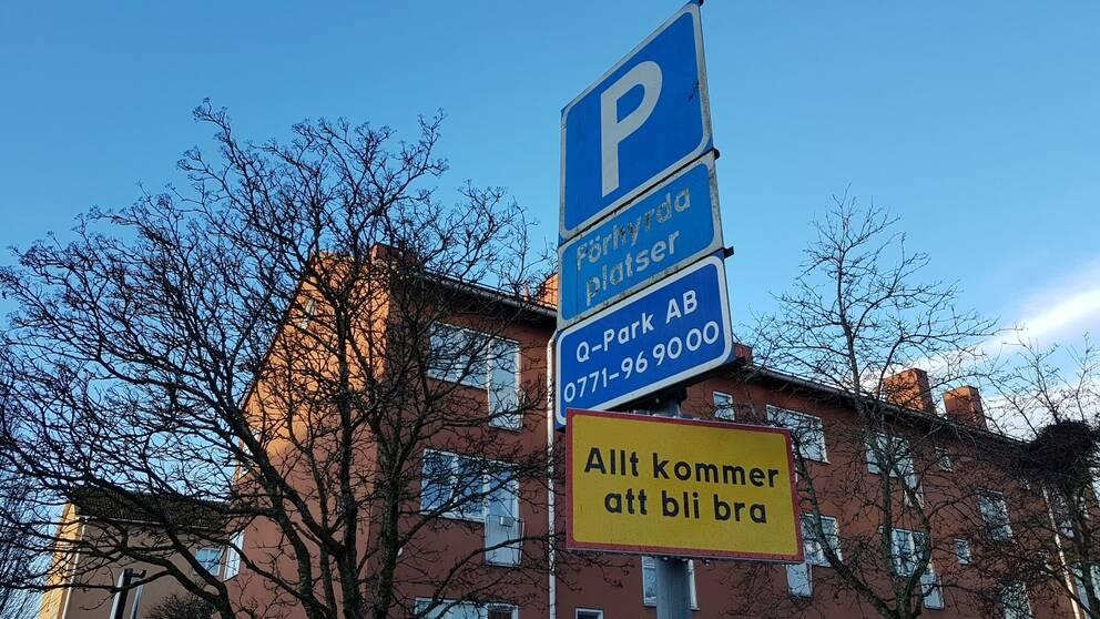 """Parkeringsskyltar och en gulröd upplysningsskylt med texten """"Allt kommer att bli bra""""."""